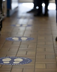 People stand besides floor stickers that encourage social distancing.