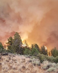 Smoke and flames from the Grandview Fire rise over the horizon on July 11.