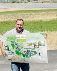 Prineville City Engineer Eric Klann holding a map of his creation, the Crooked River Wetlands Project.