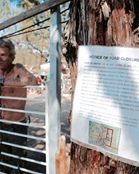 Hawk, a 6-year resident stands out front of his camp with the posted notice of closure