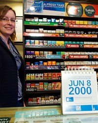 Justine Rhoads stands in front of the cigarette display at the Bond Street Market, Tuesday, Jan. 16. Although the new smoking age took effect Jan. 1, Rhoads said the Oregon Health Authority sent out a sell-by calendar that still shows 18 years of age as the sell-to date. Rhoads said only out-of-state teens had attempted to buy tobacco.