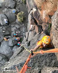 Young girls rope in their confidence on a sheer rock face.