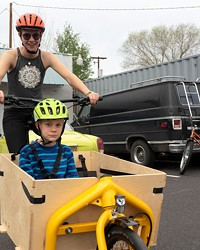 Willow Hamilton rides Aidan Miller around in a Bakfiets-style bike in the parking lot of Bend Electric Bikes.