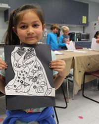 A student displays her artwork from an enrichment activity with Kids Inc. at Juniper Elementary.