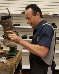 Keeping shoes out of overflowing landfills is one of Lonnie Patrick's goals. Here, he refurbishes 20-year-old boots.