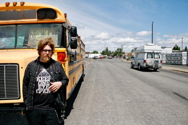 Zach Polton stands outside of his school bus, turned home on Northeast First Street in Bend. - CHRIS MILLER