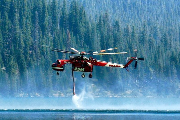 A helicopter picks up water to douse a fire on McKay Ridge in the Deschutes National Forest on Monday 7/29. - CHARLES BLUMENTHAL