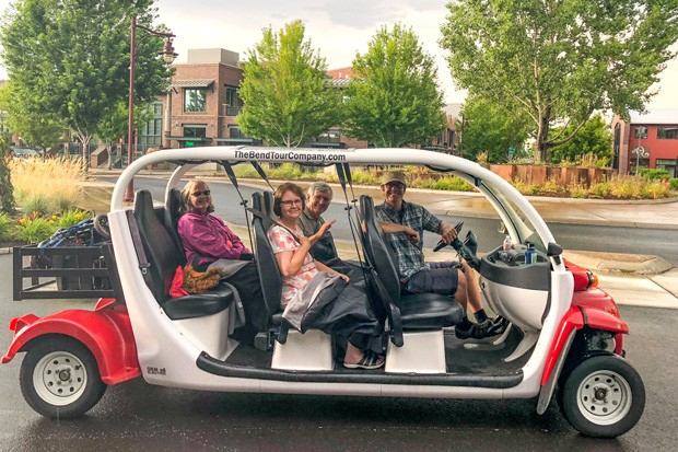 John Flannery and fellow art adventurers in The Bend Tour Company's open-air electric car. - TEAFLY PETERSON