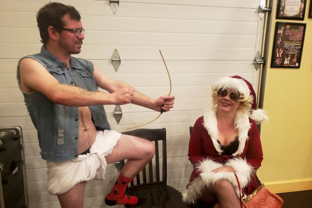 Michael Daidone, AKA Cupid, makes a pass at Melinda Rees Jahn, AKA Mrs. Claus. - CAYLA CLARK