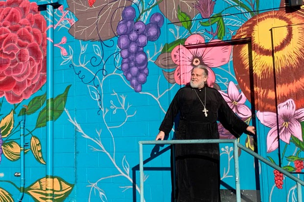 Father Damian Kuolt in front of the colorful mural on the side of the bookstore, painted by artist 