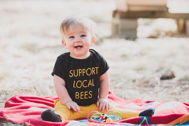 Jimmy Wilkie's daughter, Delilah June, happily supports local bees. - AMANDA PHOTOGRAPHIC