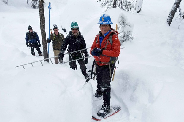 In their snowy elements, volunteers work on installing trail markers. - CENTRAL OREGON NORDIC CLUB