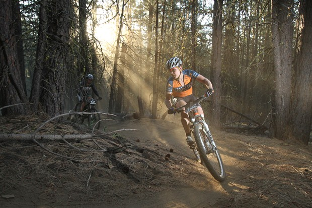 A rider soaks up the filtered rays on course running through the dense forests. - COURTESY MUDSLINGER EVENTS