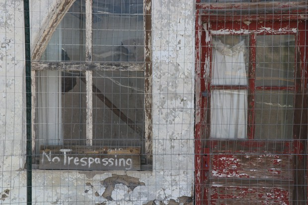 A 'No Trespassing' sign is left outside a decaying building in Brothers. - JACK HARVEL
