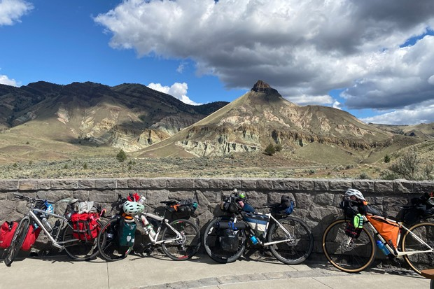 The author's cobbled-together gravel/touring bike, second from left, bought on Craigslist for less than a new Arcteryx down puffy. Also front panniers, bought on an online marketplace for less than a new pair of Tevas. - NICOLE VULCAN