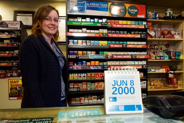 Justine Rhoads stands in front of the cigarette display at the Bond Street Market, Tuesday, Jan. 16. Although the new smoking age took effect Jan. 1, Rhoads said the Oregon Health Authority sent out a sell-by calendar that still shows 18 years of age as the sell-to date. Rhoads said only out-of-state teens had attempted to buy tobacco. - SOURCE STAFF