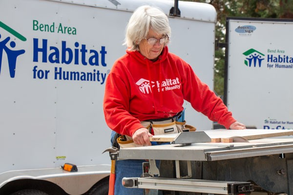 Ann Kelly, a volunteer with Bend Area Habitat for Humanity, uses a table saw to modify a cabinet shelf at the new construction site Monday. The nonprofit is building two new homes at NW 17th Street and NW Hartford  Street. - KEELY DAMARA