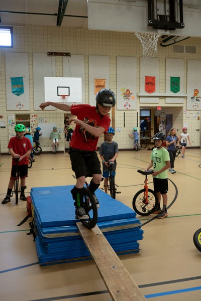Jon DeGraff rides across a plank during the Pine Ridge Elementary's Unicycle Club practice. - CHRIS MILLER