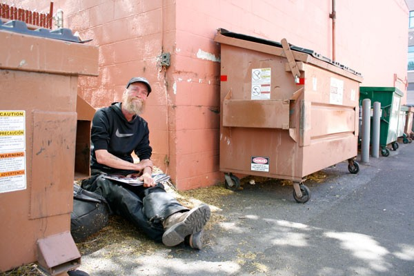 Bill Smith sits between two dumpsters in the alleyway by Pedego Electric Bikes in Bend. - CHRIS MILLER