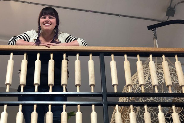 Pastry Chef and Owner Nickol Hayden-Cady looks out at the cafe as she rests her arms on the rolling pin-adorned railing. - LISA SIPE
