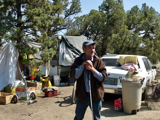 Mark, who is blind, leans on his cane in front of his camp on COID property east of Redmond Tuesday. - CHRIS MILLER