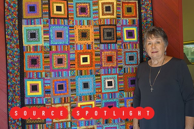 """Kathy Chism stands beside """"Robins Take the Steps,"""" a log cabin-style work that will be featured in the Sisters Outdoor Quilt Show in July. - ELIZABETH WARNIMONT"""