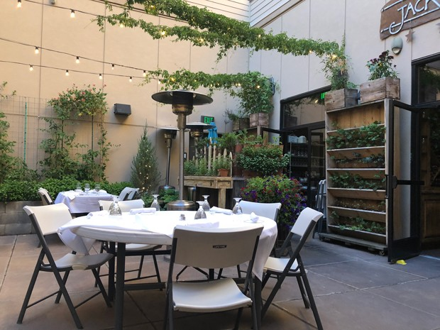 The hidden courtyard inside Jackalope Grill, surrounded by natural greenery, a garden and fairy lights, is a relaxing setting for dinner. - LISA SIPE
