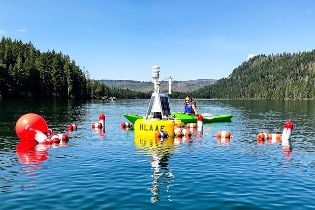 The High Lakes Aquatic Alliance Foundation data buoy in Suttle Lake, with the photographer's granddaughter, Chayse Teeple, looking it over. - CONRAD WEILER