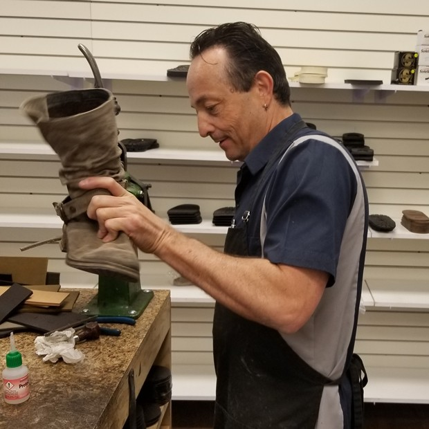 Keeping shoes out of overflowing landfills is one of Lonnie Patrick's goals. Here, he refurbishes 20-year-old boots. - LYNN LEWIS
