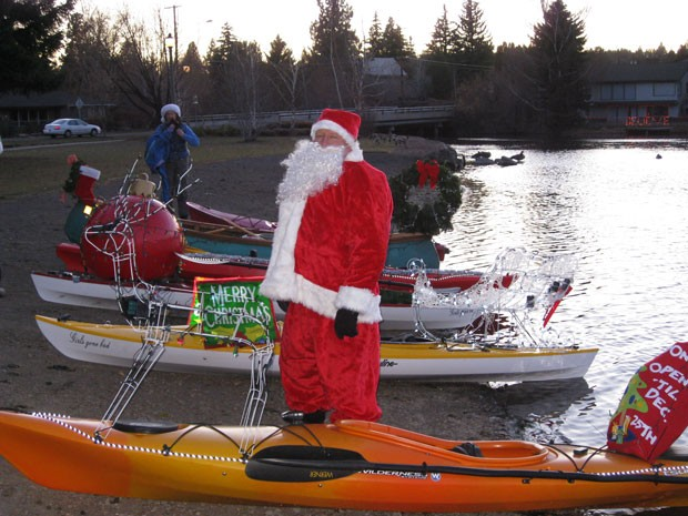 A jolly Old Saint Nick stands next to his festive kayak at the Holiday Lights Paddle Parade. - TUMALO CREEK KAYAK & CANOE