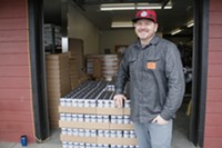 Cascade Armory's Alex Short standing next to a pallet of Blunder Armour.