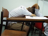 A student sleeps at his desk in Thailand.