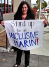 A woman protests outside the forum with the Canal Alliance.