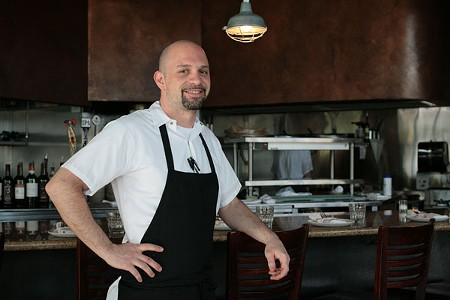 Chef Ryan Favini in front of Tavola's wide-open kitchen. - GABE MELINE