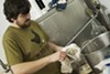 <b>MOLLUSK & SPICE</b> HenHouse's Shane Goepel shucks oysters for a batch of oyster stout.</p>