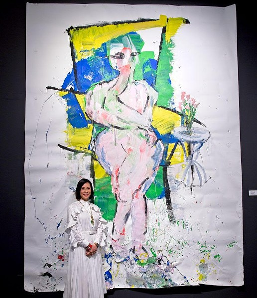 "Lucy Liu stands in front of her large-scale painting, ""Hunger."" - LOWELL DOWNEY"