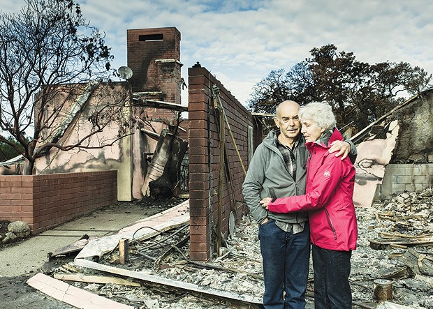 STILL STANDING Fire survivors Johann and Gloria Heinzl pose in front of the remains of their home 