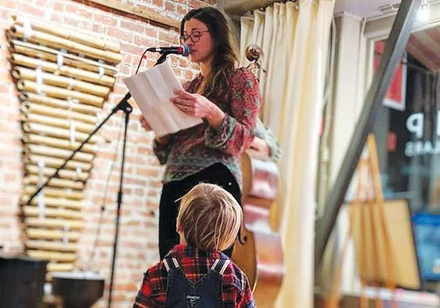 BUMPER CROP Stacy Tuel reads at Bump Wine Cellars as her son Otis cheers her on. - AJ PETERSEN
