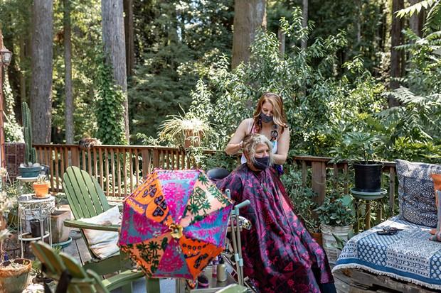 Graton-based hairstylist Ramona Camille cuts hair amid a redwood grove.