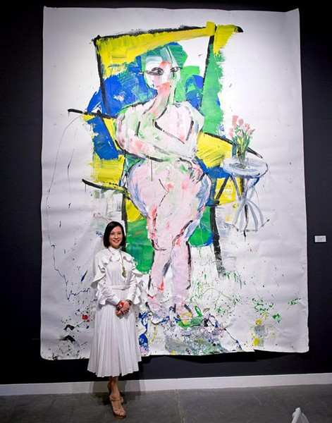 """Lucy Liu stands in front of her large-scale painting, """"Hunger."""" - LOWELL DOWNEY"""