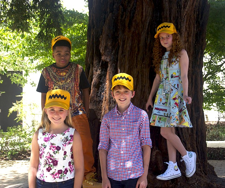 The young cast poses in the courtyard of the Charles M Schulz Museum with their sweet Peanuts-themed hats