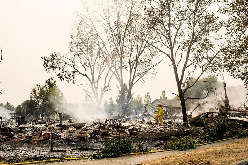 A firefighter hoses down hotspots where a home once stood in the Coffey Park neighborhood. - DAWN HEUMANN