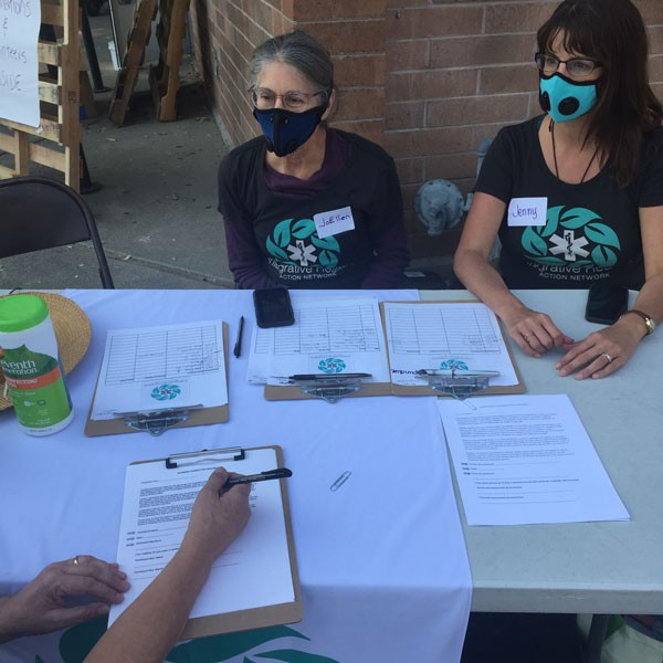 Jenny Harrow and JoEllen DeNicola of the Integrative Healers Action Network sign up evacuees for alternative therapies at the Kenilworth Recreation Center.