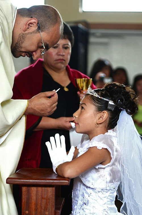 """A young girl receives a spiritual meal, her first communion in the Catholic church"" by Trevor Normile"