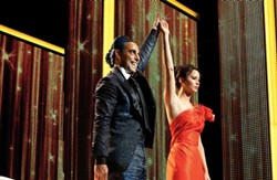 LIONSGATE - AMERICAN IDOL: TV host Caesar Flickerman (Stanley Tucci) introduces Katniss Everdeen (Jennifer Lawrence) to the masses in The Hunger Games.