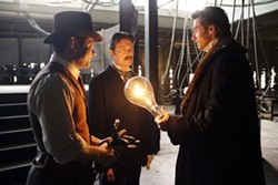 FRANCOIS DUHAMEL/TOUCHSTONE & WARNER - AN ILLUMINATING DISCUSSION: Tesla (David Bowie, center) and his assistant Alley (Andy Serkis, left) shed some light on an enigmatic matter for Angier (Hugh Jackman) in The Prestige.