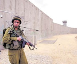 ELI MARGALIT - An Israeli soldier patrols The Wall.