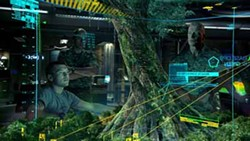 WETA - CAN'T SEE THE FOREST FOR THE TREE: Jake (Sam Worthington, left) tries to explain to Quaritch (Stephen Lang) that the Na'vi are linked to their planet's environment in Avatar.