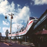 Carowinds' old monorail system as it rounds a curve, passing under the also-gone Skyway Cable Lift and above the Oaken Bucket ride.