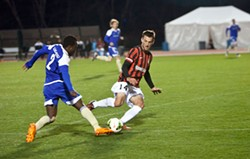 PHOTOS BY JEFF HAHNE - Charles Eloundou works past a Charleston Battery defender during the debut game of the Charlotte Independence on March 27.